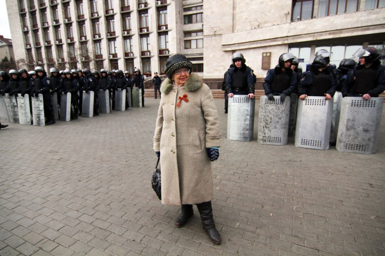 A woman wearing a pro-Russian ribbon stands near Ukrainian police officers outside the regional administration building in the eastern Ukrainian city of Donetsk on March 5, 2014. (Reuters photo)