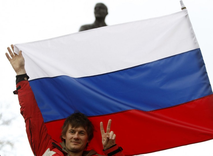 A pro-Russian supporter poses in front of a Russian flag at a meeting in Simferopol on March 5, 2014. (REUTERS/Vasily Fedosenko)
