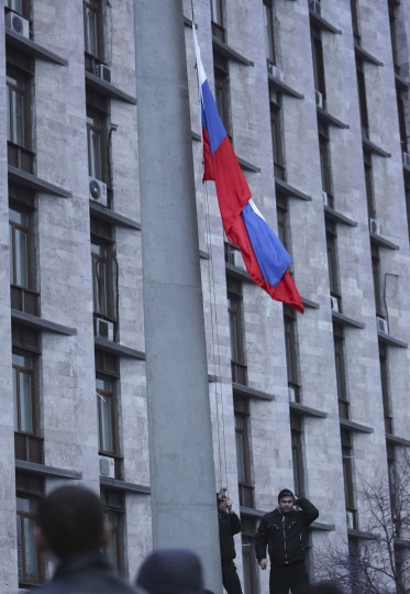 Pro-Russian demonstrators raise a Russian flag outside the regional government building in Donetsk on March 5, 2014. (REUTERS/Valeriy Bilokryl)