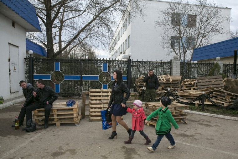 A woman and children walk in front of pro-Russian supporters who are blocking the gate to the Ukrainian Navy headquarters in Sevastopol, Crimea, on March 6, 2014. (REUTERS/Baz Ratner)
