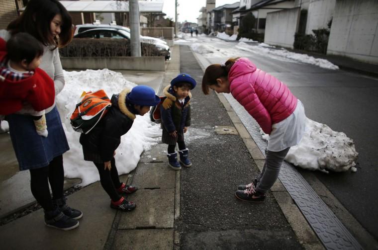 Children bow to greet their nursery school teacher (right) as they get into a school bus heading to the Emporium kindergarten in Koriyama, west of the tsunami-crippled Fukushima Daiichi nuclear power plant, Fukushima prefecture on February 28, 2014. (REUTERS/Toru Hanai)