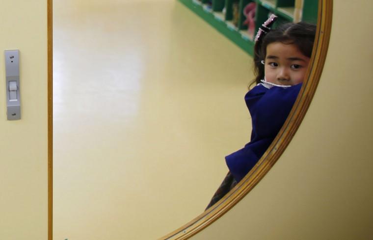 A girl opens the door of a teacher's staff room at the Emporium kindergarten in Koriyama, west of the tsunami-crippled Fukushima Daiichi nuclear power plant, Fukushima prefecture on February 28, 2014. (REUTERS/Toru Hanai)