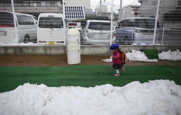 A girl runs past a geiger counter, measuring a radiation level of 0.122 microsievert per hour, upon her arrival at the Emporium kindergarten in Koriyama, west of the tsunami-crippled Fukushima Daiichi nuclear power plant, Fukushima prefecture on February 28, 2014. (REUTERS/Toru Hanai)