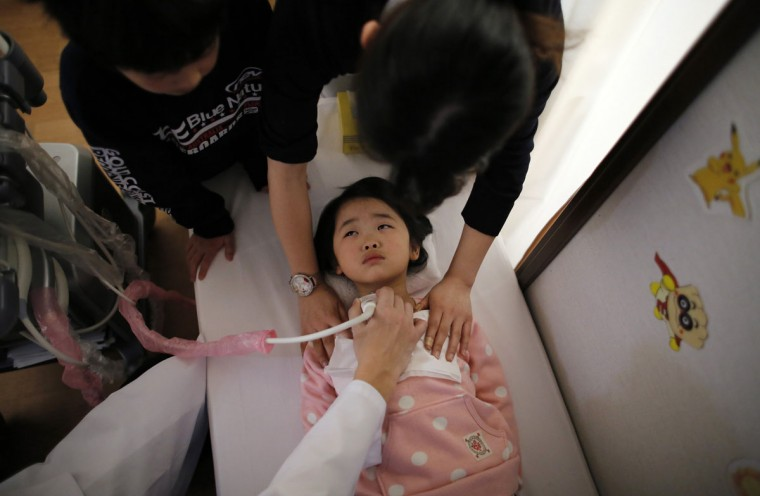 A doctor conducts a thyroid examination on a five-year-old girl as her older brother and a nurse take care of her at a clinic in temporary housing complex in Nihonmatsu, west of the tsunami-crippled Fukushima Daiichi nuclear power plant, Fukushima prefecture on February 27, 2014. (REUTERS/Toru Hanai)