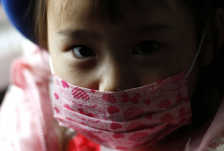 A girl wearing a mask sits in a school bus heading to the Emporium kindergarten in Koriyama, west of the tsunami-crippled Fukushima Daiichi nuclear power plant, Fukushima prefecture on February 28, 2014. (REUTERS/Toru Hanai)
