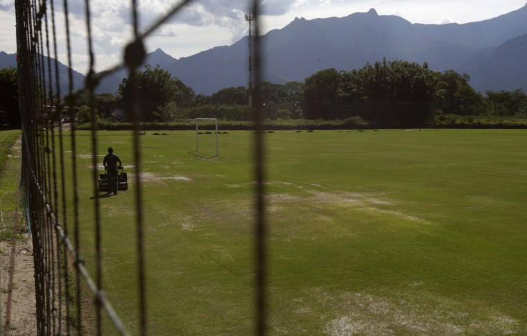 A man works on the soccer field at Portobello Resort, where the Italy soccer team will be based during the 2014 World Cup, in Mangaratiba. (REUTERS/Ricardo Moraes)