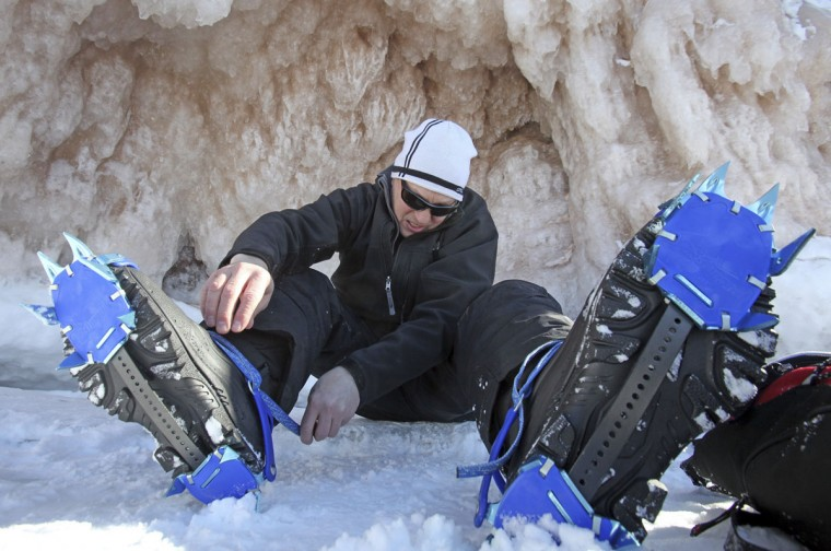 Jeff Neddo, from Eagle River, Wis., tightens new crampons on his boots at the sea caves of the Apostle Islands National Lakeshore of Lake Superior near Cornucopia, Wis., on February 14, 2014. (REUTERS/Eric Miller)
