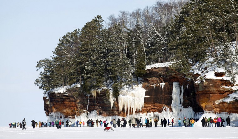 Sightseers trek across a frozen expanse of Lake Superior, the world's largest freshwater lake, to the sea caves of the Apostle Islands National Lakeshore near Cornucopia, Wis., on February 14, 2014. (REUTERS/Eric Miller)