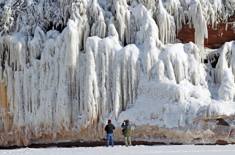 Sightseers look at a frozen rock face along the Apostle Islands National Lakeshore of Lake Superior, the world's largest freshwater lake, near Cornucopia, Wis., on February 14, 2014. (REUTERS/Eric Miller)