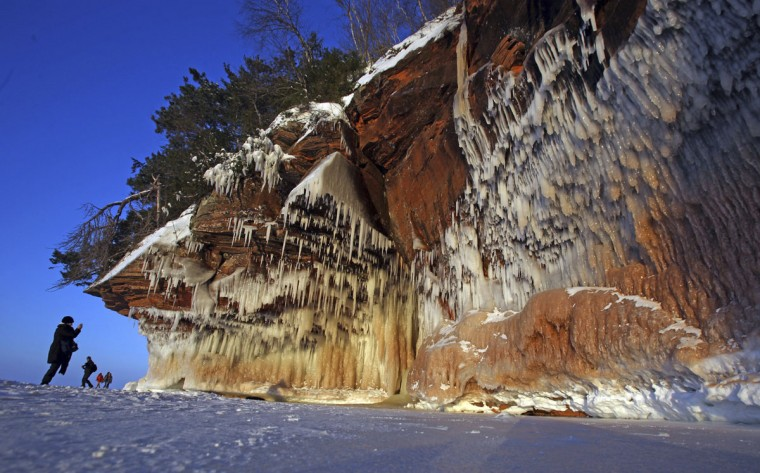A woman photographs ice formations at sunset on a rock face of the Apostle Islands National Lakeshore of Lake Superior, the world's largest freshwater lake, to the sea caves near Cornucopia, Wis., on February 14, 2014. According to the National Oceanic and Atmospheric Administration (NOAA) Great Lakes Environmental Research Laboratory, about 94% of Lake Superior is covered with ice, enabling thousands of people to visit the islands on foot for the first time since 2009. The Great Lakes, which contain one fifth of the world's surface fresh water, are 88% covered with ice. (REUTERS/Eric Miller)