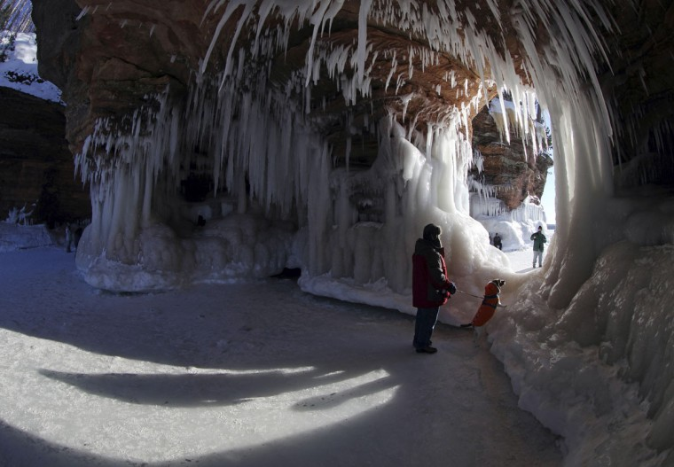 Pete Miller, from Minong, Wis., looks through an opening with his dog at the sea caves of the Apostle Islands National Lakeshore of Lake Superior near Cornucopia, Wis. (REUTERS/Eric Miller)