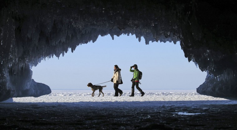 Sightseers are framed by the icicles of a sea cave as they trek across a frozen expanse of Lake Superior, the world's largest freshwater lake, at the Apostle Islands National Lakeshore near Cornucopia, Wis. (REUTERS/Eric Miller)