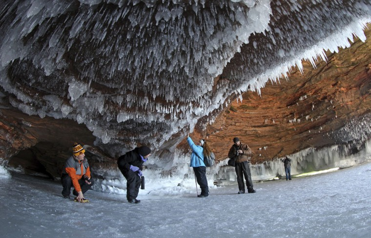 Sightseers crouch to avoid icicles in a sea cave on frozen Lake Superior, the world's largest freshwater lake, at the Apostle Islands National Lakeshore near Cornucopia, Wis., on February 14, 2014. (REUTERS/Eric Miller)