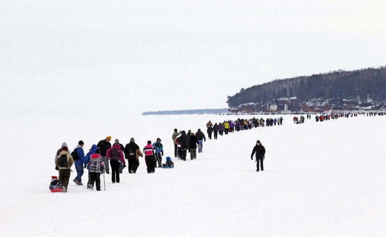 Sightseers trek across a frozen expanse of Lake Superior, the world's largest freshwater lake, to the sea caves of the Apostle Islands National Lakeshore near Cornucopia, Wis., on February 15, 2014. (REUTERS/Eric Miller)