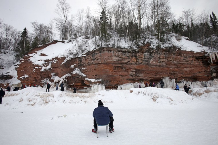 A man rests on frozen Lake Superior, the world's largest freshwater lake, at the sea caves of the Apostle Islands National Lakeshore near Cornucopia, Wis., on February 15, 2014. (REUTERS/Eric Miller)