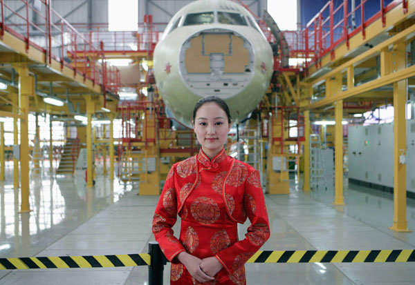 A staff member stands in front of the new Airbus A320 family final assembly line at its assembly plant in Tianjin Municipality on September 28, 2008. (REUTERS/China Daily)
