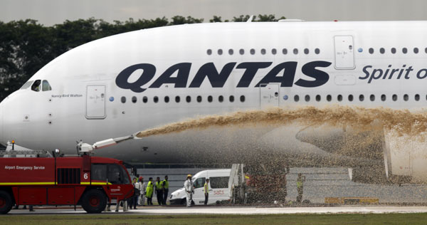 Qantas Airways 380 passenger plane flight QF32 is sprayed by rescue services after making an emergency landing at Changi airport in Singapore on November 4, 2010. (REUTERS/Vivek Prakash)
