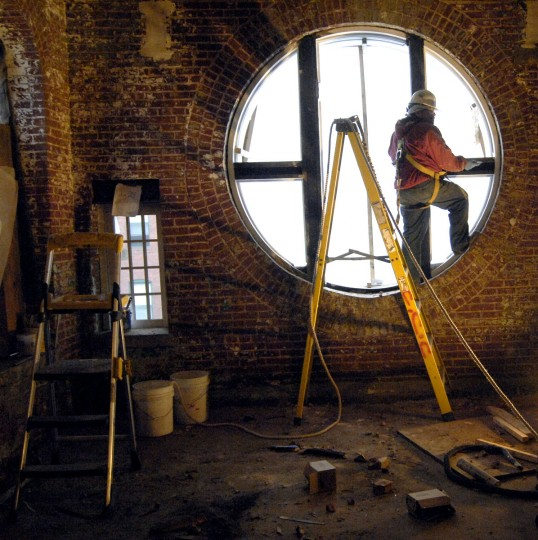 Workers frame the windows on the second floor of the American Brewery Company building on Gay Street. (Christopher T. Assaf / Baltimore Sun)