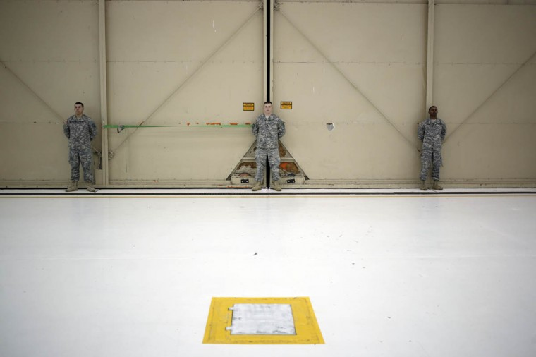 Army troops from the 101st Airborne Division stand along a hangar door while awaiting the arrival of troops from the U.S. Army's Battery B, 2nd Battalion, 44th Air Defense Artillery Regiment to a homecoming ceremony at Campbell Army Airfield March 21, 2014 in Fort Campbell, Kentucky. About 60 soldiers returned to Fort Campbell after a nine-month combat deployment providing artillery and mortar support for coalition forces in Afghanistan. (Luke Sharrett/Getty Images)