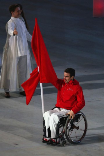 Christoph Kunz of Switzerland bears a flag during the Opening Ceremony of the Sochi 2014 Paralympic Winter Games at Fisht Olympic Stadium on March 7, 2014 in Sochi, Russia. (Hannah Peters/Getty Images)