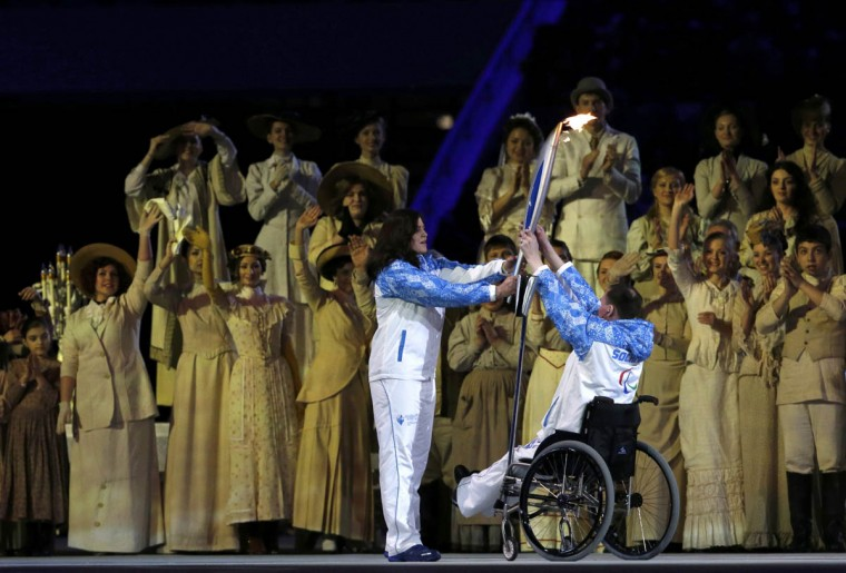 Four-time track and field Paralympic champion and record-holder Aleksey Ashapatov of Russia (Right), hands the torch to his compatriot and Paralympic champion Olga Semenova, during in the opening ceremony of the 2014 Paralympic Winter Games in Sochi, March 7, 2014. (Alexander Demianchuk/Reuters photo)