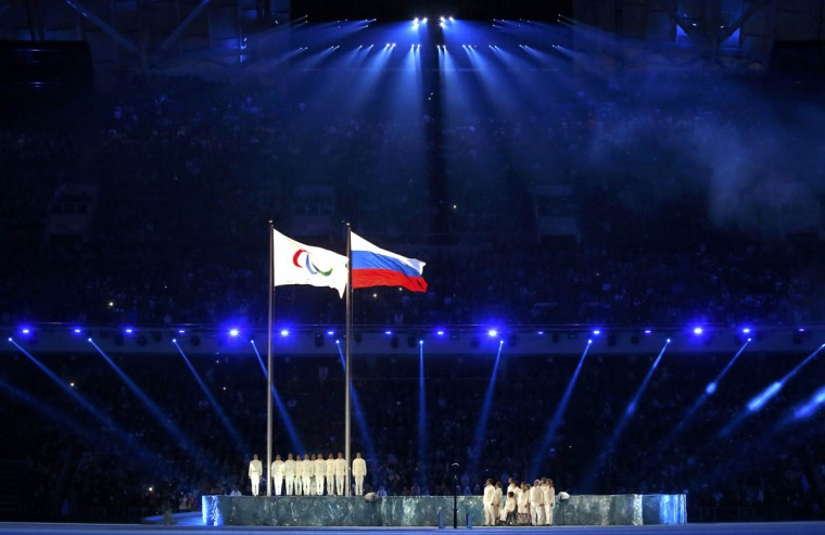 The Paralympic flag (Left), is seen besides the Russian national flag during the opening ceremony of the 2014 Paralympic Winter Games in Sochi, March 7, 2014. (Alexander Demianchuk/Reuters photo)
