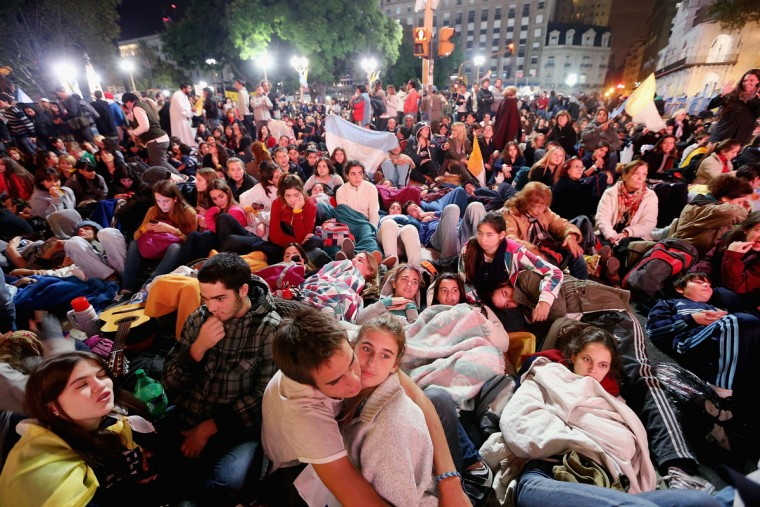 Argentinians sit in Plaza de Mayo during an overnight vigil while waiting to watch a live broadcast of the installation of Pope Francis in Saint Peter's Square on March 19, 2013 in Buenos Aires, Argentina. Francis was the archbishop of Buenos Aires and is the first Pope to hail from Latin America. Celebrants watched in the early morning hours as the event was broadcast at 6:00 a.m. Buenos Aires time. (Photo by Mario Tama/Getty Images)