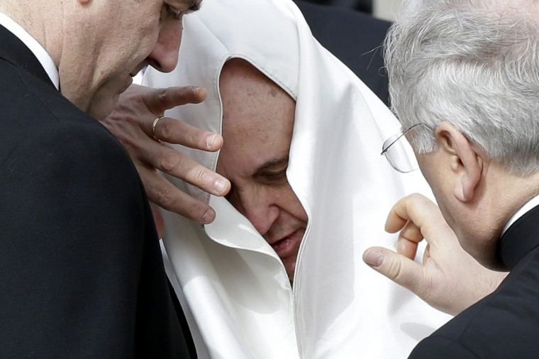 Pope Francis is helped with his mantle after it was moved by a gust of wind during the general audience in Saint Peter's Square at the Vatican February 19, 2014. (REUTERS/Max Rossi)