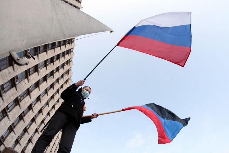 """A pro-Russian protester waves a Russian flag (L) and the so-called flag of the Donetsk Republic in front of the regional administration building during a rally in the industrial Ukrainian city of Donetsk on March 1, 2014. More than 10,000 people carrying Russian flags protested in the eastern Ukrainian city of Donetsk, the stronghold of ousted president Viktor Yanukovych. Protesters declared they supported """"the aspirations of Crimea to rejoin Russia"""", referring to Ukraine's pro-Russia peninsula further south where Kiev has accused Moscow of launching an """"armed invasion."""" (Alexander Khudoteply/AFP/Getty Images)"""