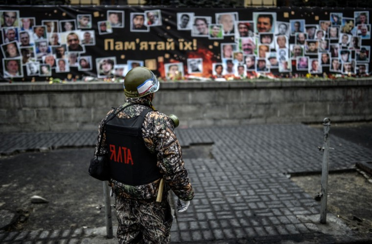 """A member of a so-called """"Maidan's self defence unit"""" looks at pictures of protesters who were killed during recent clashes, displayed in central Kiev on March 1, 2014. Ukraine's defence chief accused Russia on March 1, 2014 of sending 6,000 troops and 30 armoured personnel carriers into Crimea as the restive peninsula tries to gain broader independence from new pro-EU leaders in Kiev. (Bulent Kilic/AFP/Getty Images)"""