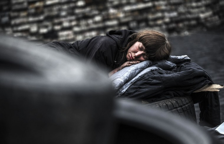 """A woman sleeps behind a barricade on Kiev's Independence square on March 1, 2014. Pro-Russian forces tightened their grip on Crimea on Saturday as the Kremlin vowed to help restore calm on the restive Ukrainian peninsula and Washington warned of """"costs"""" to Moscow should it order in troops. (Bulent Kilic/AFP/Getty Images)"""