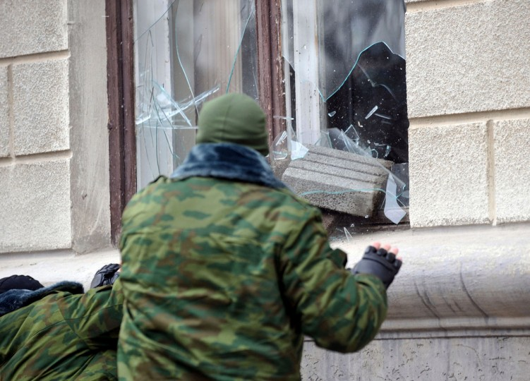 """Unidentified masked individuals throw a concrete block through a window as they storm the Trade Union building in Semferopol, the administrative center of Crimea, on March 1, 2014. Russia's parliament on March 1 gave President Vladimir Putin the go-ahead to send troops into Ukraine, despite a warning from Washington that such a deployment would results in """"costs"""" for Moscow. The stark escalation of the ex-Soviet country's three-month political crisis came amid growing instability in Ukraine's predominantly Russian peninsula of Crimea that has housed Kremlin navies for nearly 250 years. (Genya Savilov/AFP/Getty Images)"""