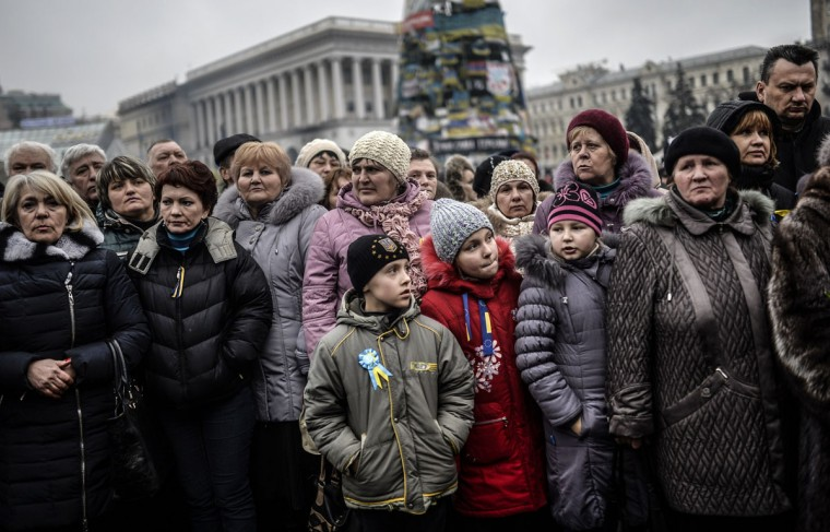 """People gather around a coffin as they attend the funeral cermony of a victim of the recent clashes with the riot police on Kiev's Independence square on March 1, 2014. Pro-Russian forces tightened their grip on Crimea on March 1, 2014 as the Kremlin vowed to help restore calm on the restive Ukrainian peninsula and Washington warned of """"costs"""" to Moscow should it order in troops. (Bulent Kilic/AFP/Getty Images)"""
