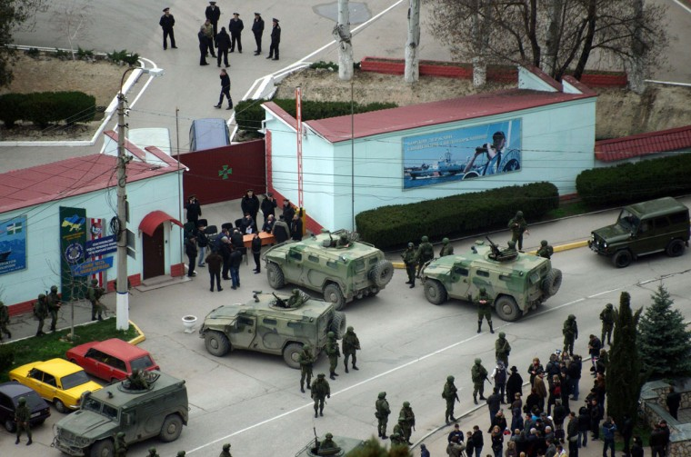 """Unidentified armed individuals with armoured vehicles block the base of the Ukrainian border guard service in Sevastopol, on March 1, 2014. Ukraine's border guard service said on March 1 that about 300 armed men were attempting to seize its main headquarters in the Crimean port city of Sevastopol under orders from Russian Defence Minister Sergei Shoigu. """"The head of this group said that there are orders from the Russian defence minister to seize this naval post,"""" Ukraine's border guard service said in a statement, adding that the men wore """"full battle fatigues"""". (Vasily Batanov/AFP/Getty Images)"""