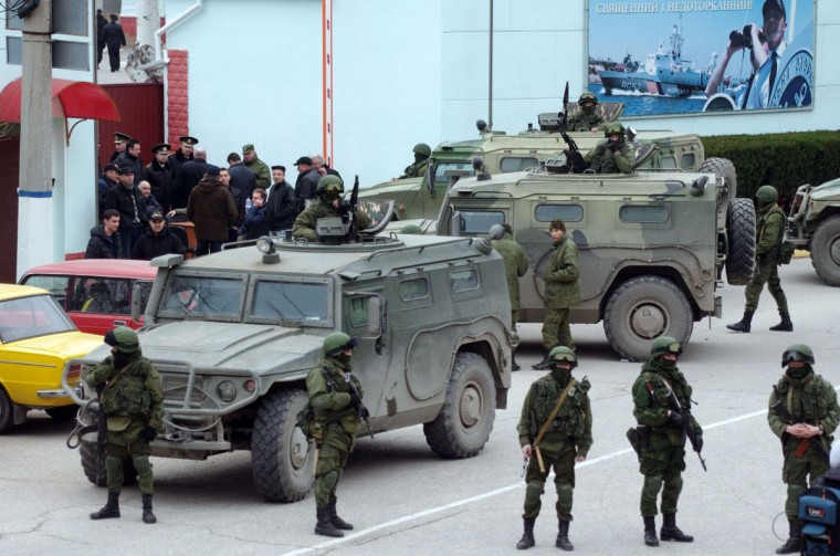 """Unidentified armed individuals with armoured vehicles block the base of the Ukrainian border guard service in Sevastopol, on March 1, 2014, near a sign (R) reading """"The border of the country is sacred and untouchable"""". Ukraine's border guard service said on March 1 that about 300 armed men were attempting to seize its main headquarters in the Crimean port city of Sevastopol under orders from Russian Defence Minister Sergei Shoigu. """"The head of this group said that there are orders from the Russian defence minister to seize this naval post,"""" Ukraine's border guard service said in a statement, adding that the men wore """"full battle fatigues"""". (Vasily Batanov/AFP/Getty Images)"""