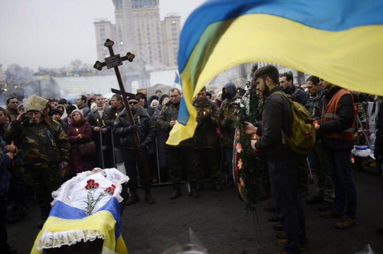 """People gather around a coffin of a man who was killed during the recent clashes with the riot police during a funeral cermony on Kiev's Independence square on March 1, 2014. Pro-Russian forces tightened their grip on Crimea on March 1, 2014 as the Kremlin vowed to help restore calm on the restive Ukrainian peninsula and Washington warned of """"costs"""" to Moscow should it order in troops. (Bulent Kilic/AFP/Getty Images)"""