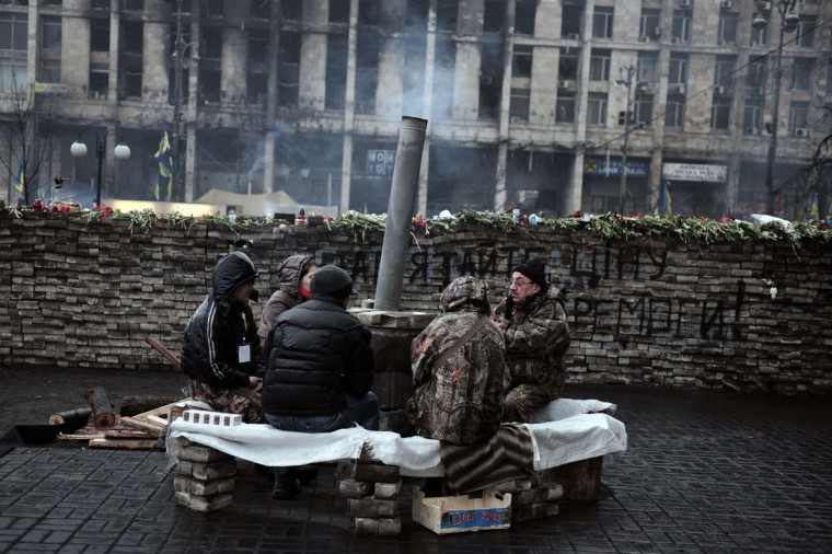 """So-called 'Maidan self defence unit ' members guard a barricade at Independence square in central Kiev on March 1, 2014. Ukraine accused Russia on March 1, 2014 of sending thousands of extra troops into Crimea as the Kremlin vowed to help restore calm on the flashpoint peninsula and Washington warned of """"costs"""" to Moscow should it use force. (Louisa Gouliamaki/AFP/Getty Images)"""