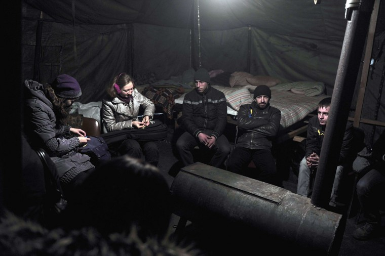 """Protesters warm up in a tent at Independence square in central Kiev on March 1, 2014. Ukraine accused Russia on March 1, 2014 of sending thousands of extra troops into Crimea as the Kremlin vowed to help restore calm on the flashpoint peninsula and Washington warned of """"costs"""" to Moscow should it use force. (Louisa Gouliamaki/AFP/Getty Images)"""