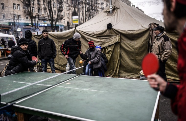 """Youths play table tennis near Kiev's Independence square on March 1, 2014. Pro-Russian forces tightened their grip on Crimea on March 1, 2014 as the Kremlin vowed to help restore calm on the restive Ukrainian peninsula and Washington warned of """"costs"""" to Moscow should it order in troops. (Bulent Kilic/AFP/Getty Images)"""
