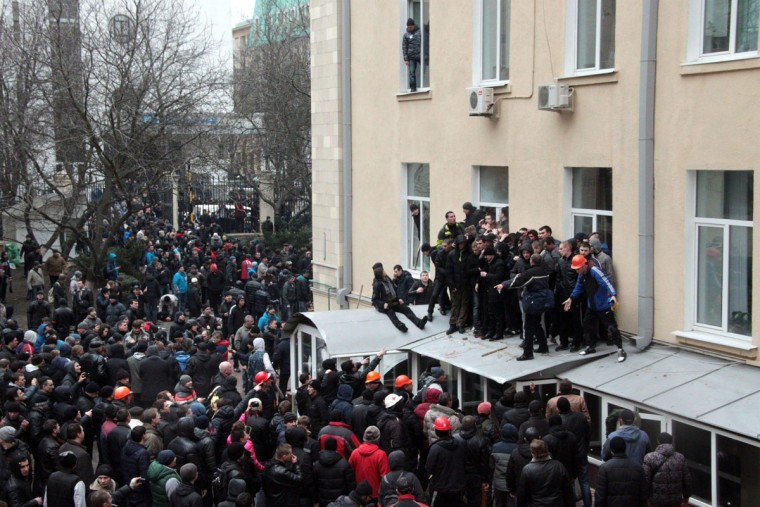 People stand on the awning outside the regional government building in Kharkiv on March 1, 2014. Dozens were hurt on March 1, 2014 when a pro-Russia protest in Ukraine's eastern city of Kharkiv turned violent, with demonstrators trying to storm the local government building. Some 20,000 joined the protest against Kiev's new pro-West government after the ouster of Kremlin-backed leader Viktor Yanukovych, and later around 300 launched the assault on the government building. Stones and stun grenades were thrown though it was unclear by whom. (Sergey Bobok/AFP/Getty Images)