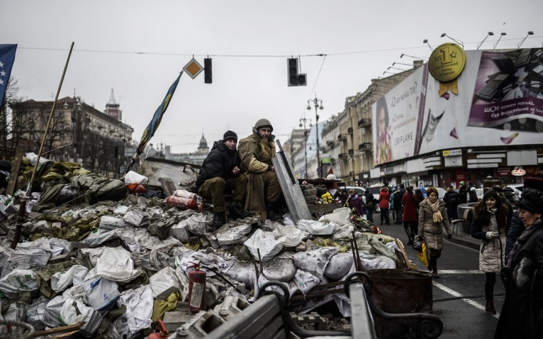 """A Maidan activist sits on a barricade at the entrance of Kiev's Independence square on March 1, 2014. Pro-Russian forces tightened their grip on Crimea on March 1, 2014 as the Kremlin vowed to help restore calm on the restive Ukrainian peninsula and Washington warned of """"costs"""" to Moscow should it order in troops. (Bulent Kilic/AFP/Getty Images)"""