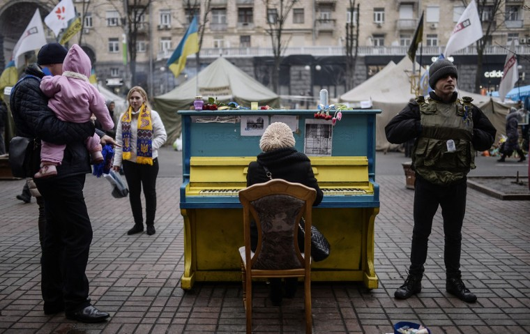 """A woman plays a piano in a street near Kiev's Independence square on March 1, 2014. Pro-Russian forces tightened their grip on Crimea on March 1, 2014 as the Kremlin vowed to help restore calm on the restive Ukrainian peninsula and Washington warned of """"costs"""" to Moscow should it order in troops. (Bulent Kilic/AFP/Getty Images)"""