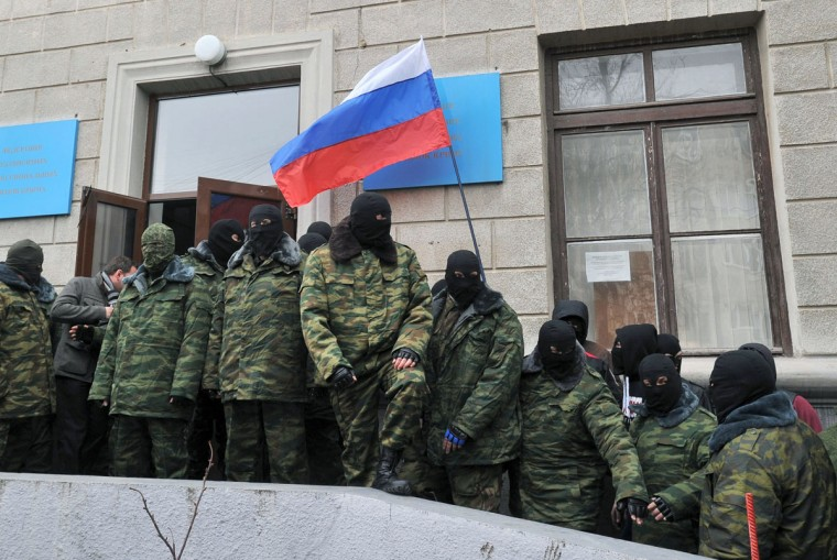 """An unidentified masked individuals hold a Russian flag as they block the Trade Union building in Simferopol, the administrative center of Crimea, on March 1, 2014. Russia's parliament on March 1 gave President Vladimir Putin the go-ahead to send troops into Ukraine, despite a warning from Washington that such a deployment would results in """"costs"""" for Moscow. The stark escalation of the ex-Soviet country's three-month political crisis came amid growing instability in Ukraine's predominantly Russian peninsula of Crimea that has housed Kremlin navies for nearly 250 years. (Genya Savilov/AFP/Getty Images)"""