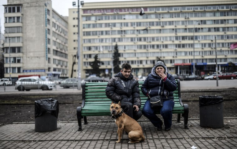 """A couple sits on a bench in central Kiev on March 1, 2014. Pro-Russian forces tightened their grip on Crimea on March 1, 2014 as the Kremlin vowed to help restore calm on the restive Ukrainian peninsula and Washington warned of """"costs"""" to Moscow should it order in troops. (Bulent Kilic/AFP/Getty Images)"""