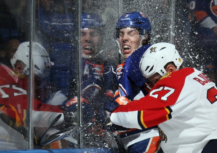 Travis Hamonic #3 of the New York Islanders is hit into the glass by Nick Bjugstad #27 of the Florida Panthers during the first period at the Nassau Veterans Memorial Coliseum on April 1, 2014 in Uniondale, New York. (Bruce Bennett/Getty Images)