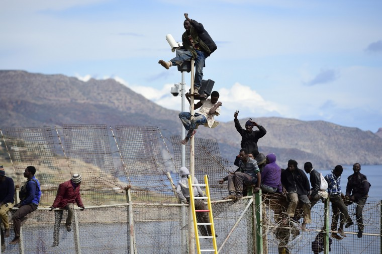 African migrants attempt to scale the fence at the border between Morocco and the North African Spanish enclave of Melilla, on April 3, 2014, in Melilla, Spain. Roughly 70 sub-Saharan migrants tried to climb the fence into Melilla this morning; one had to be treated by paramedics. Melilla is a Spanish city and an exclave on the north coast of Africa sharing a border with Morocco.  (Photo by Alexander Koerner/Getty Images)