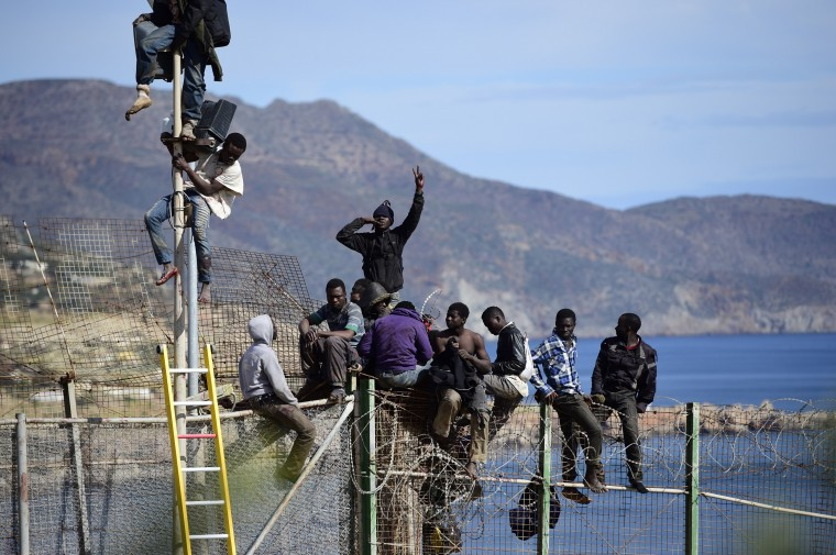 African migrants attempt to scale the fence at the border between Morocco and the North African Spanish enclave of Melilla, on April 3, 2014, in Melilla, Spain. Roughly 70 sub-Saharan migrants tried to climb the fence into Melilla this morning, one had to be treated by paramedics. Melilla is a Spanish city and an exclave on the north coast of Africa sharing a border with Morocco. Almost one week ago some 800 sub-Saharan people made several attempts to reach Spain and according to official sources, ten of them managed to enter Spanish territory. (Photo by Alexander Koerner/Getty Images)