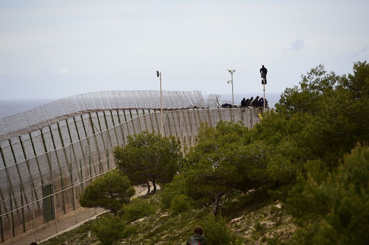Migrants attempt to scale the fence at the border between Morocco and the North African Spanish enclave of Melilla. In order to get across the border, migrants must get over three layers of fencing.  (Photo by Alexander Koerner/Getty Images)