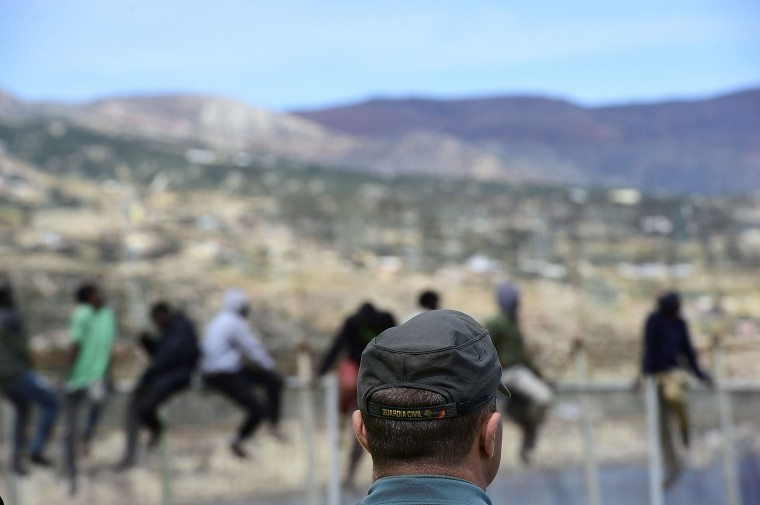 Guardia Civil Officers watch African migrants attempt to scale the fence at the border between Morocco and the North African Spanish enclave of Melilla, on April 3, 2014, in Melilla, Spain. Roughly 70 sub-Saharan migrants tried to climb the fence into Melilla this morning; one had to be treated by paramedics. Melilla is a Spanish city and an exclave on the north coast of Africa sharing a border with Morocco.  (Photo by Alexander Koerner/Getty Images)