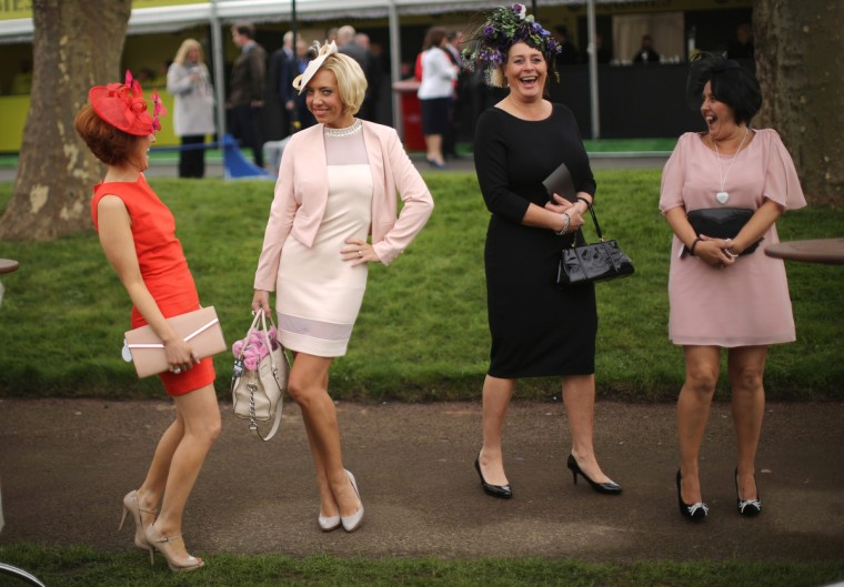 Racegoers enjoy the atmosphere of Ladies Day and dress to impress at the Aintree Grand National Festival meeting on April 4, 2014 in Aintree, England. Friday is traditionally Ladies day at the three-day meeting of the world famous Grand National Festival where fashion and dressing to impress is as important as the racing. (Christopher Furlong/Getty Images)